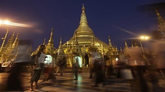 A foreign tourist pauses to look at the glittering Shwedagon Pagoda in Yangon, Myanmar.