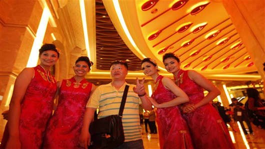 FILE - In this May 15, 2011 file photo, a mainland Chinese visitor is welcomed by hostess at Galaxy Macau as the multibillion-dollar casino resort opened in Macau. Galaxy Entertainment Group plans to double the size of its flagship Macau casino in a $2.1 billion expansion as it seeks to win over more customers in the world's biggest gambling market. The Hong Kong company said it has already started construction of the second phase of its Galaxy Macau casino complex, which opened last year in the