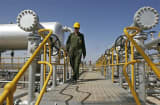 FILE - An Iranian oil technician makes his way to the oil separator facilities in Iran's Azadegan oil field southwest of Tehran.