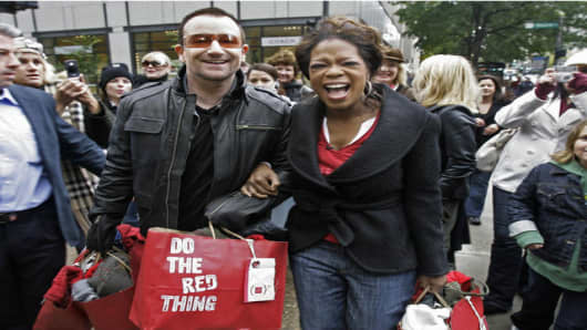 "Irish rocker Bono, frontman for U2, and talk show host Oprah Winfrey walk down Chicago's ""Magnificent Mile"" Thursday, Oct. 12, 2006, for a shopping spree to promote Bono's new RED line of clothing, accessories and gadgets that w"