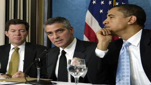 Academy Award winning actor George Clooney, center, flanked by Sen. Barack Obama, D-Ill., right, and  Sen. Sam Brownback, R-Kan., takes part in a news conference at the National Press Club in Washington, Thursday, April 27, 2006 to bring awareness to the situation in the Darfur region of Sudan. (AP Photo/Mannie Garcia)