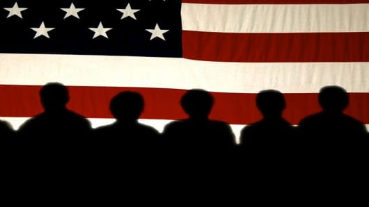 Supporters are silhouetted on a flag as they listen to Vice President Dick Cheney speak at a town hall meeting, Tuesday, Sept. 28, 2004 in Dubuque, Iowa. (AP Photo/Charlie Neibergall)