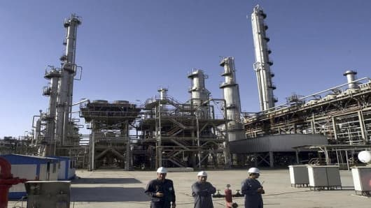 Workers stand in a part of the Bandar Imam Petrochemical Company (BIPC) facility during an official opening ceremony by President Mohammad Khatami, in Mahshahr, Iran, Saturday, June 11, 2005. BIPC is one of the largest industrial establishments in the Islamic Republic of I
