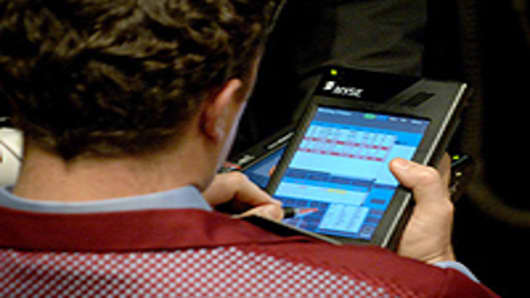 A trader on the floor of the New York Stock Exchange executes a trade with his NYSE E-Broker.