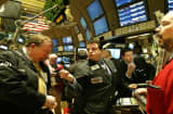 Traders at SIG Specialists trading post on the floor of the New York Stock Exchange talk among themselves shortly after the opening bell Monday, April 18, 2005, in New York.  Stocks regained some stability Monday following a three-day selloff as strong first-quarter earnings and a pair of merger announcements lent some support to a market battered by worries about economic growth.  (AP Photo/Kathy Willens)