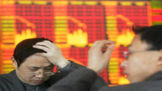 Stock investors watch stock movement at a stock exchange in Chengdu, China.