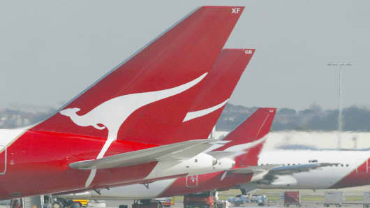 Qantas passenger jets parked at their terminal at Sydney Airport.