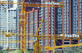 Cranes stand on a construction site in front of newly completed apartment buildings in Beijing.