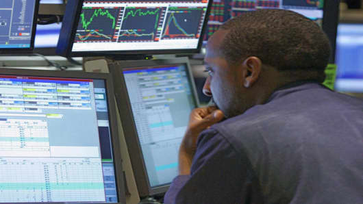 A specialist is surrounded by screens as he works at his post on the floor of the New York Stock Exchange, Tuesday, June 5, 2007. Stocks dipped Tuesday after comments from Federal Reserve Chairman Ben Bernanke and a strong reading on the U.S. service sector suggested the central bank has