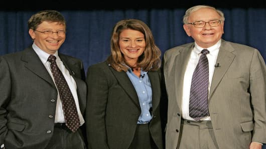 Bill Gates, left, Melinda Gates and Warren Buffett pose for a picture after a press conference Monday, June 26, 2006 in New York.  Warren Buffett, the chairman of Berkshire Hathaway, recently announced his intention of giving 10 million shares of his company to charitable organizations, the majority going to the Bill and Melinda Gates Foundation.  (AP Photo/Seth Wenig)
