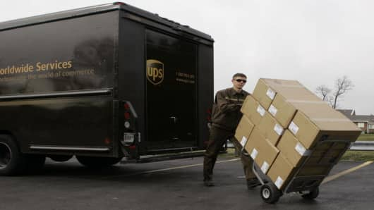 A United Parcel Service driver pushes a load of packages.