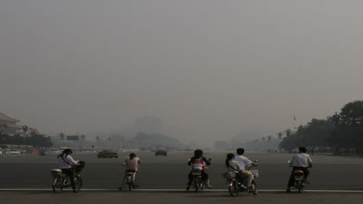 Cyclists and bikers stop at a traffic light, as buildings are faintly seen, rear, shrouded in a haze of smog in Beijing. (AP Photo/Shuji Kajiyama)