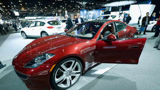 Reporters gather around a Fisker Karma during the Los Angeles Auto show on November 29, 2012 in Los Angeles, California.