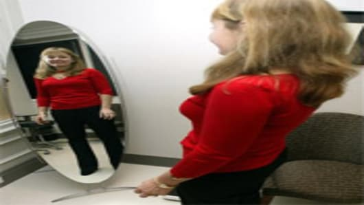 Woman looks at herself in a mirror at cosmetic surgeon office
