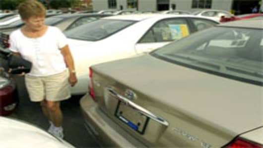 Woman looks at new Toyota Camry on dealer lot