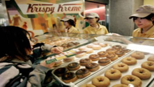A customer orders doughnuts at a Krispy Kreme store in Tokyo's Shinjuku district during a lunch break. Since opening in December, Japan's first Krispy Kreme Doughnuts Inc. store is drawing long lines for an hour long wait, or longer, just to get in. In the first three days, 10,000 people came to the shop. (AP Photo/Vincent Thian)