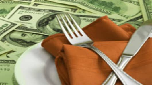 Fork and knife, place setting on money, cutlery on napkin with plate, expensive food