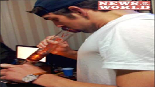 Michael Phelps inhales from a bong