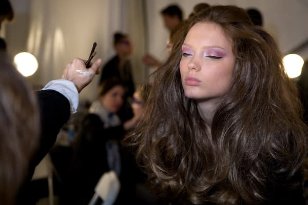 A model gets make up  backstage.