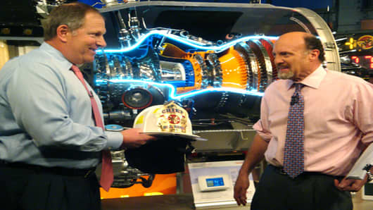 Honeywell CEO David Cote presents Cramer with a special fire chief's helmet. That's a real jet engine behind them.