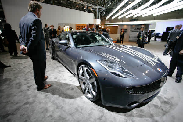 An onlooker observes the 2009 Fisker Karma, with plug-in hybrid technology called Q DRIVE, developed by Quantum Technologies exclusively for Fisker Automotive. The Karma's Q DRIVE configuration consists of a small gasoline engine that turns the generator, which charges the lithium ion battery pack, powering the electric motor and turning the rear wheels.  Estimated price starts at $80,000.