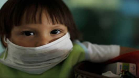 Young boy wearing protective mask against possible swine flu