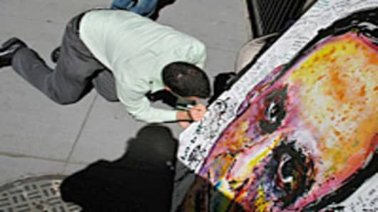 Man signing painting of Richard Fuld