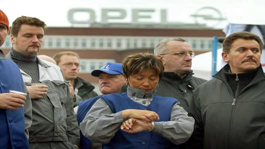 Workers of the Opel plant, a subsidiary of General Motors, in Bochum, western Germany, block the entrance gate on Monday Oct. 18, 2004. Workers protest against plans of the carmaker's parent company General Motors to cut some 10,000 jobs in Germany. (AP Photo/Frank Augstein)