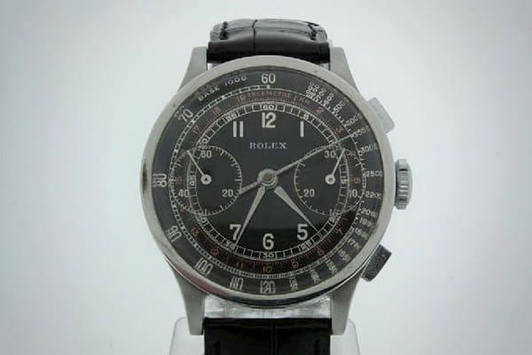 A professionally restored vintage Rolex watch with a black dial, white numbers and black alligator strap.