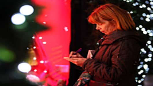 A woman makes a shopping list in front of a department store's Christmas window display.