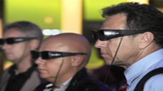 Fairgoers wear special '3D' glasses as they watch a movie on a 3D TV screen.