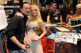 A fan has his photo taken with adult film actress Jesse Jane at the Digital Playground booth at the 2010 AVN Adult Entertainment Expo in Las Vegas, Nevada.