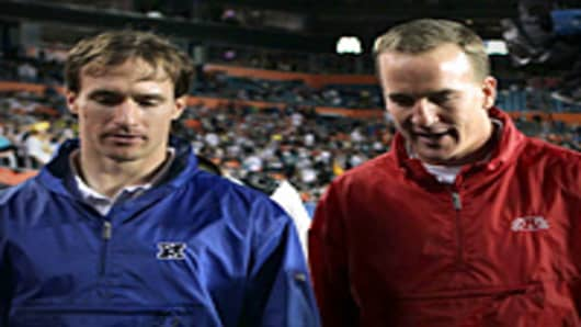 Drew Brees of the New Orleans Saints and Peyton Manning of the Indianapolis Colts walk on the field during 2010 AFC-NFC Pro Bowl at Sun Life Stadium.