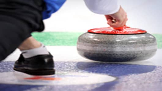A competitor releases his stone during the men's curling round robin game between Germany and the United States at the Vancouver 2010 Winter Olympics.