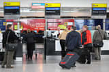 Passengers are pictured at Check-In desks at London's Heathrow airport.