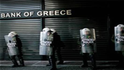 Riot police line up outside a closed branch of the National Bank of Greece during a 24-hour general strike.