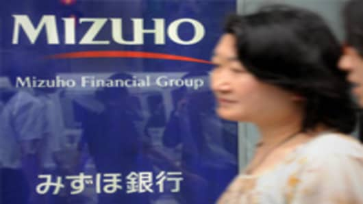 Women walk past the logo of Japan's second-largest bank Mizuho Financial Group in Tokyo.