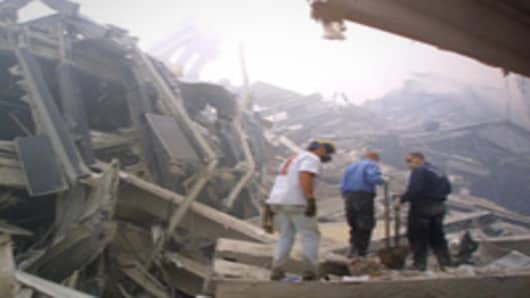 Rescue workers search through the rubble of the twin towers at the World Trade Center in lower Manhattan 11 September, 2001.