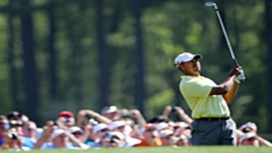 Tiger Woods hits a shot as fans look on during a practice round prior to the 2010 Masters Tournament at Augusta National Golf Club.