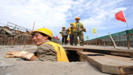 Workers assist at a construction site of the Chengdu-Dujiangyan railway.