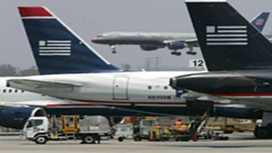 A United Airlines jet lands as US Airways jets are prepared for flight at Los Angles International Airport.