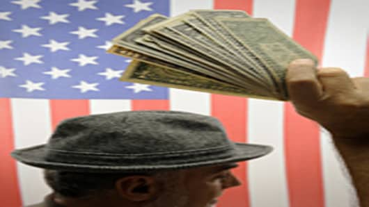Man's hand raised with US dollars over US flag