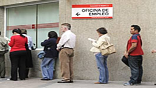People wait in line at a government employment office in the center of Madrid.