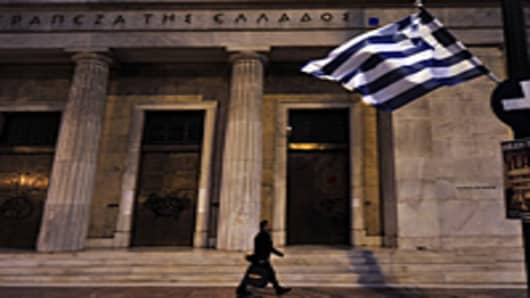 A man walks outside the Bank of Greece headquarters during a demonstation against government's austerity measures in central Athens.