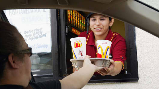 Josephine Hernandez hands a tray of drinks to a drive thru customer at a McDonald's restaurant i