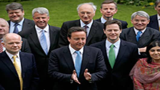 Britain's Prime Minister David Cameron (front 2nd Left) calls an end to a group picture with his new cabinet ministers in the garden of Number 10 Downing Street in London, England.