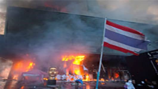 A Thai National Flag is seen inside the devastated red shirt camp as a fire burns at the Central World Shopping Mall.