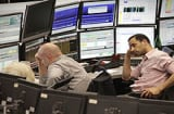 Traders sit in front of their screens at the stock exchange in Frankfurt/Munich, western Germany.