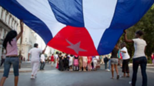 Women carrying Cuban flag through Havana streets.