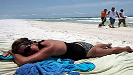 Woman lies on the beach as workers clean up tar balls on the Gulf Islands National Seashore, Pensacola Beach, Florida.
